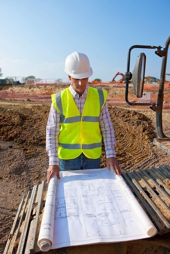 Architect reviewing blueprints at construction site : Stock Photo
