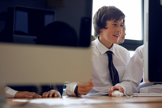 Students in school uniform using computers : Stock Photo
