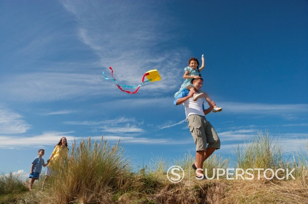 Family with kite on sunny beach : Stock Photo