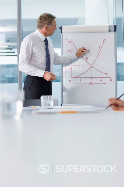 Businessman writing on chart in conference room : Stock Photo