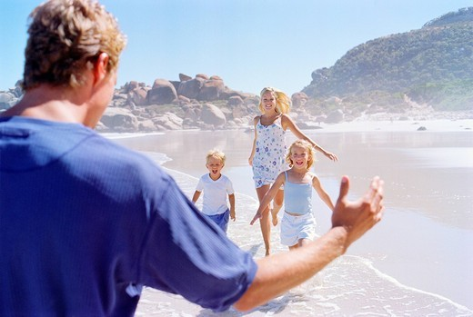 Father greeting family running toward him on beach : Stock Photo