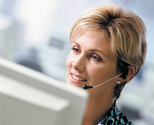 Smiling businesswoman in headset working at computer : Stock Photo
