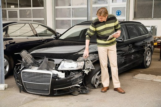 Insurance adjuster assessing damage to car : Stock Photo