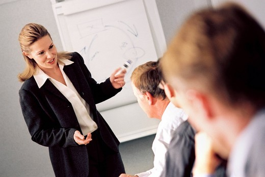Business people watching co_worker giving presentation and drawing on flip chart : Stock Photo