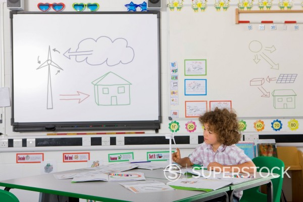Curious student examining model wind turbine in school classroom : Stock Photo