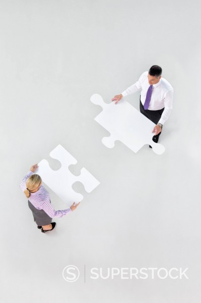 Stock Photo: 4208R-29346 Businessman and businesswoman holding large jigsaw pieces