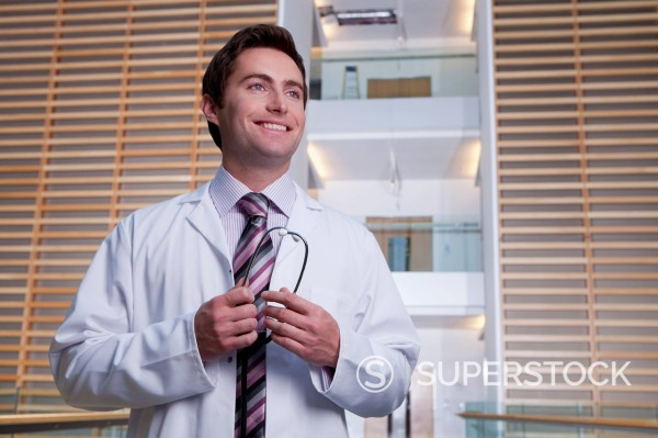 Stock Photo: 4208R-29640 Portrait of smiling doctor wearing lab coat in hospital corridor
