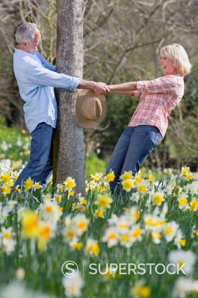 Stock Photo: 4208R-29728 Smiling senior couple holding hands around tree trunk in sunny daffodil field