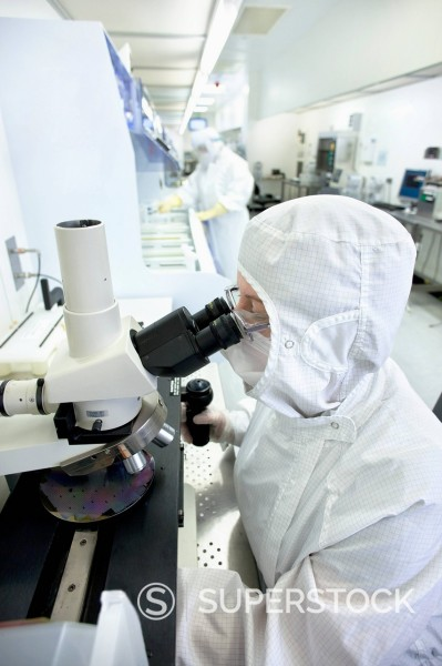 Stock Photo: 4208R-29785 Scientist in clean suit examining silicon wafer under microscope in clean room laboratory