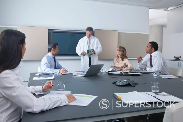 Stock Photo: 4208R-29841 Engineer showing business people electronics part in conference room
