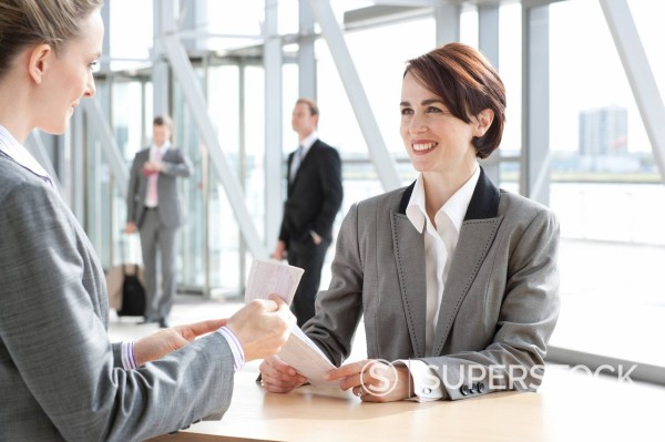 Stock Photo: 4208R-30038 Woman checking businesswomanÕs passport at airport counter