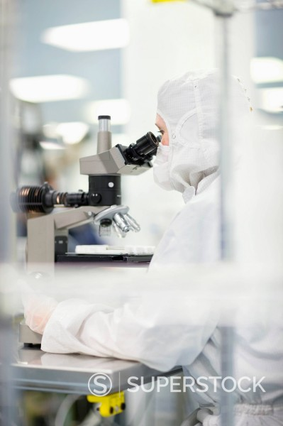 Stock Photo: 4208R-30064 Scientist in clean suit examining silicon wafer under microscope in clean room laboratory