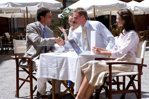 Business people working and shaking hands at sunny, outdoor cafe : Stock Photo