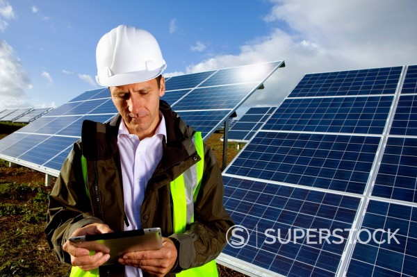 Engineer with digital tablet standing in front of solar panels : Stock Photo