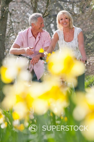 Stock Photo: 4208R-30892 Smiling senior couples with bicycles in sunny daffodil field