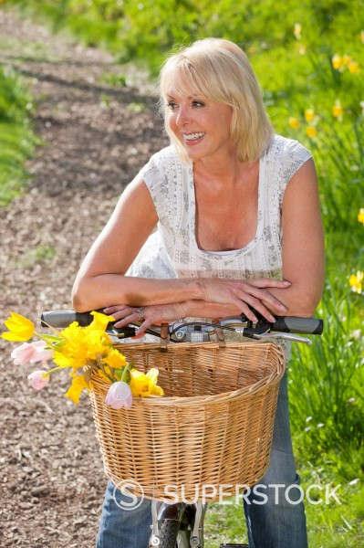 Stock Photo: 4208R-30895 Smiling woman leaning on bicycle with spring flowers in basket