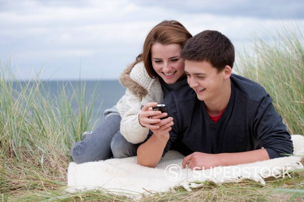 Teenage couple text messaging on cell phone in grass on beach : Stock Photo