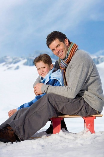 Father and son sitting on sled in snow : Stock Photo