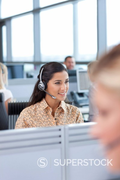 Stock Photo: 4208R-31205 Brunette businesswoman wearing headset in office
