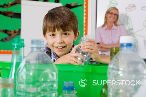 Stock Photo: 4208R-31243 Smiling student putting glass into recycling bin