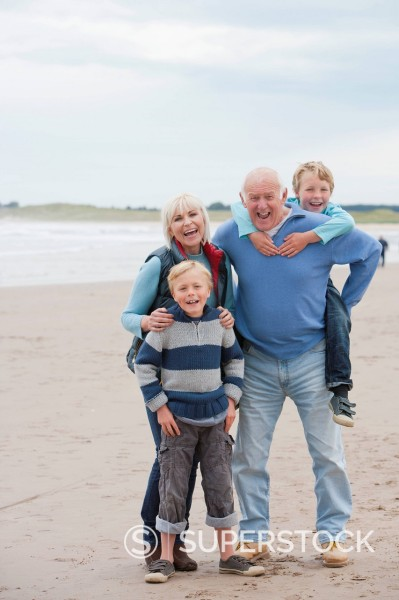 Stock Photo: 4208R-31475 Grandparents And Grandchildren Walking Along Beach Together