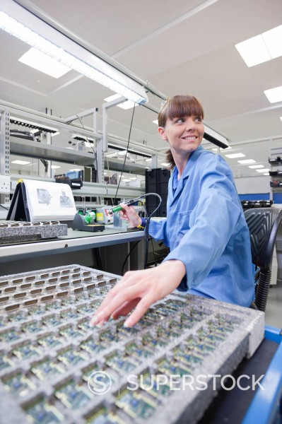 Stock Photo: 4208R-31708 Technician working on assembly line in hi_tech electronics manufacturing plant