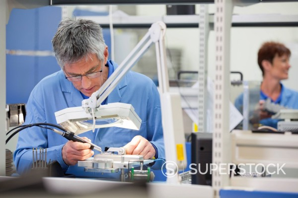 Stock Photo: 4208R-31731 Technician working on assembly line in hi_tech electronics manufacturing plant