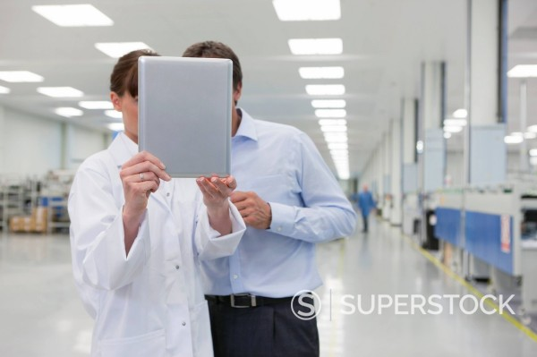 Stock Photo: 4208R-31732 Scientist and businessman looking at digital tablet in hi_tech manufacturing plant