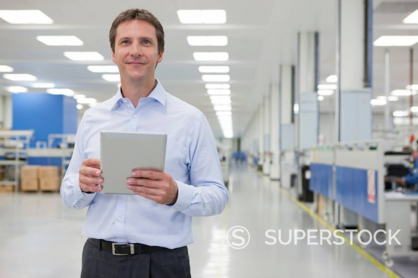 Stock Photo: 4208R-31738 Portrait of smiling businessman with digital tablet in hi_tech manufacturing plant