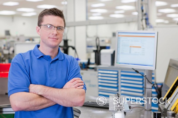 Stock Photo: 4208R-31789 Portrait of technician with arms crossed in hi_tech manufacturing plant