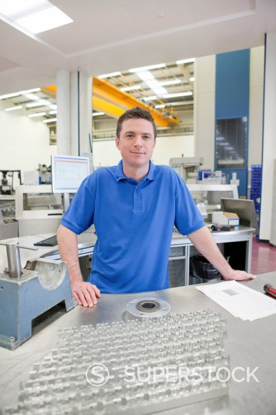 Stock Photo: 4208R-31792 Portrait of smiling technician with aluminum products in hi_tech manufacturing plant