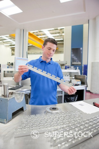 Stock Photo: 4208R-31793 Technician examining aluminum products in hi_tech manufacturing plant
