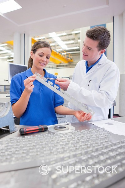 Stock Photo: 4208R-31796 Scientist and technician examining aluminum products in hi_tech manufacturing plant