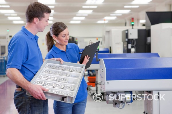 Technicians with clipboard and aluminum products near lathe cutting machine in hi_tech manufacturing plant : Stock Photo