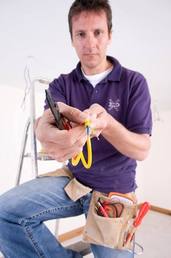 Electrician holding spliced wires : Stock Photo