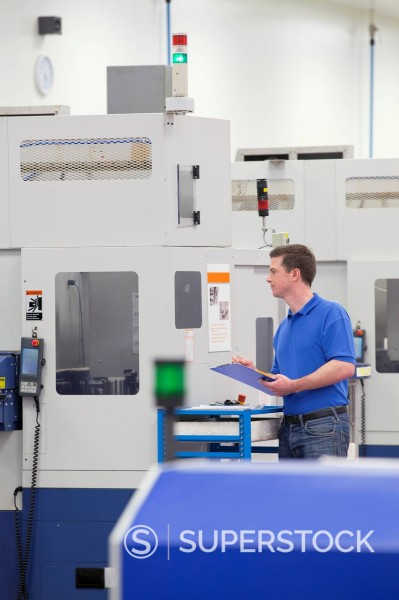 Technician with clipboard examining lathe cutting machine in hi_tech manufacturing plant : Stock Photo