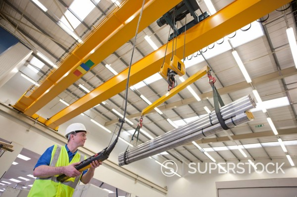 Stock Photo: 4208R-31827 Technician operating hoist with raw aluminum in hi_tech manufacturing plant