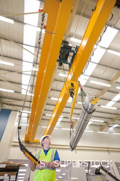 Stock Photo: 4208R-31829 Technician operating hoist with raw aluminum in hi_tech manufacturing plant