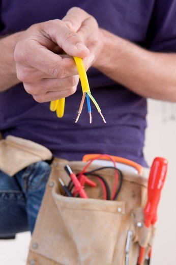 Stock Photo: 4208R-3183 Close up of electrician holding spliced wires