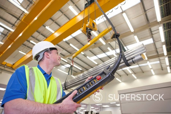 Stock Photo: 4208R-31830 Technician operating hoist with raw aluminum in hi_tech manufacturing plant
