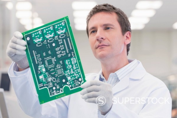 Engineer examining printed circuit board in manufacturing plant : Stock Photo