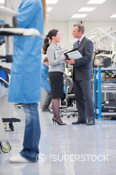 Business people meeting in manufacturing plant : Stock Photo