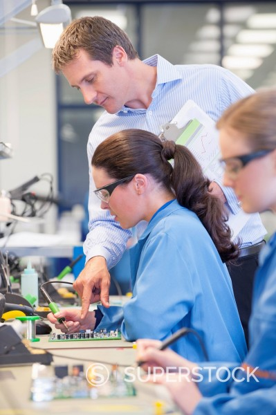 Stock Photo: 4208R-31873 Supervisor training technician to solder circuit board on production line in manufacturing plant