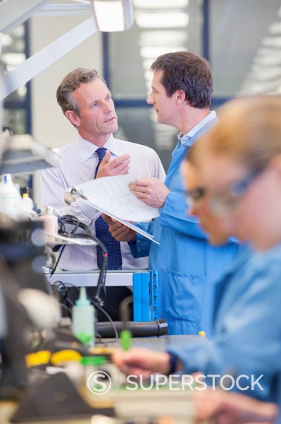 Businessman and engineer talking at production line in circuit board manufacturing plant : Stock Photo