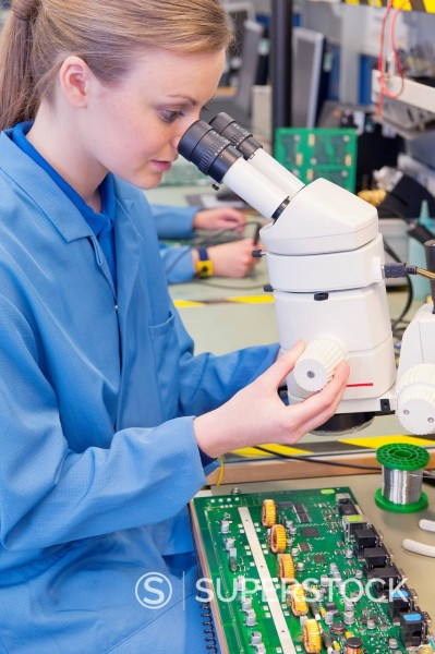 Technician using microscope to examine circuit board in manufacturing plant : Stock Photo