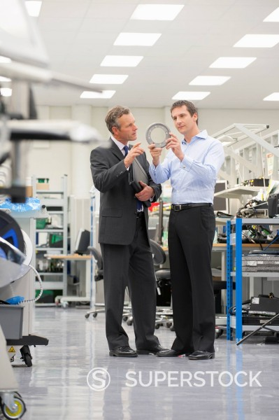 Stock Photo: 4208R-31884 Businessmen examining machine part in manufacturing plant