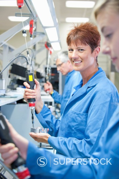Portrait of smiling technician using electric screwdriver to assemble machine part in manufacturing plant : Stock Photo