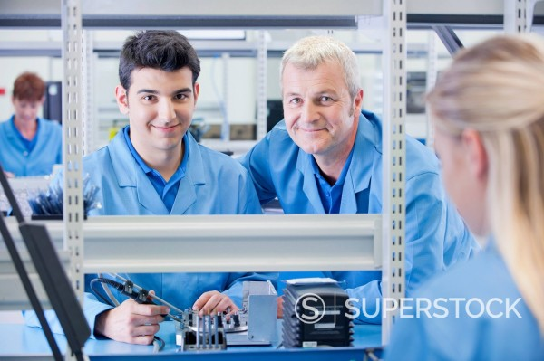 Stock Photo: 4208R-31932 Portrait of smiling supervisor and technician assembling circuit board in manufacturing plant