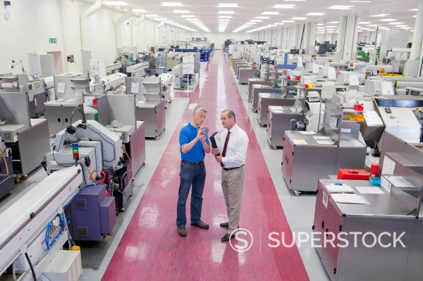 Stock Photo: 4208R-31941 Businessman and engineer inspecting part in manufacturing plant