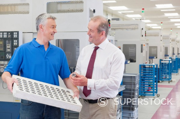 Smiling engineer and businessman examining finished machine parts in manufacturing plant : Stock Photo
